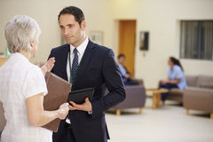 Two Consultants Discussing Patient Notes In Hospital Stock Photo