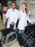 Two consultants selling wheelchairs. Two consultants in white overalls offering wheelchairs in special store with orthopaedic goods Royalty Free Stock Photography