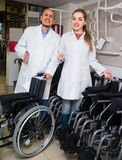 Two consultants selling wheelchairs. Two consultants in white overalls selling wheelchairs in special store with orthopaedic goods Royalty Free Stock Photography