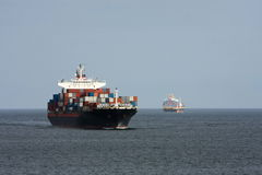 Two container ships pass at sea. Two large container ships pass ech other at sea Stock Photography