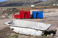 Two containers and a rusty bath tub in volcanic landscape Stock Photography
