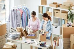 Two contemporary women packing online orders of clients in office. Two contemporary women standing by workplace while packing online orders of clients in office stock photography