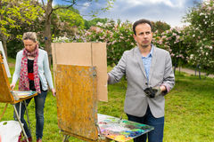 Two conteplative middle-aged fashionable artists during painting. On a sketchbook in a park Royalty Free Stock Photography