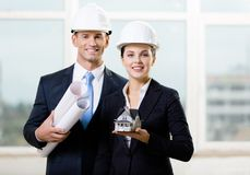 Two contractors keeping blueprints and model house Stock Image