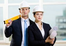 Two contractors keeping level and blueprints. Two contractors in white hard hats keeping level and blueprints. Concept of successful construction Stock Photography