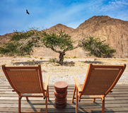Two convenient chaise lounges. And small table stand for tourists. Walking route on picturesque Black canyon royalty free stock photo