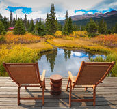 Two convenient wattled chaise lounges beside  lake Royalty Free Stock Image