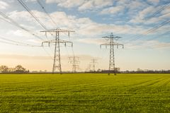 Two converging high-voltage lines in a rural area. Backlit image of two converging high voltage lines in a rural Dutch landscape in the fall season Stock Image
