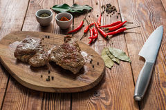 Two cooked steak with some spices on wooden table. Two cooked steak with chili pepper, some spices on wooden table royalty free stock photos