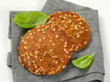 Cookies with chopped nuts and almonds. Two cookies with chopped nuts and almonds on grey place mat - close up Stock Image