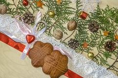 Two cookies with red ribbon and lace trim, chocolate heart at the bows and twigs of thuja. Are at an angle on a wooden plywood Royalty Free Stock Image