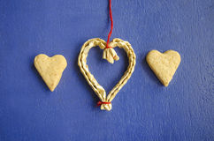 Two cookies in the shape of hearts on a blue background and hanging heart made of straw. Love concept background. February 14 holi. Days. Happy valentines day royalty free stock photo