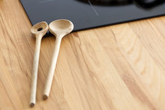 Two Cooking Spoon lies on Worktop nearby Ceramic Hob Royalty Free Stock Photo