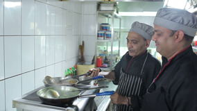Two cooks cooking dishes at kitchen restaurant stock video