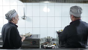 Two cooks prepare the meal at kitchen restaurant stock video footage