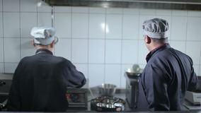 Two cooks are preparing the dishes at the kitchen. Restaurant. One of the cook mix the meal at the hot stove. The chef mix the dish with a scoop stock footage