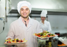 Two cooks at restaurant kitchen Royalty Free Stock Image