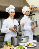Two cooks at restaurant kitchen Royalty Free Stock Photo