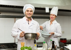 Two cooks at restaurant kitchen Royalty Free Stock Photos