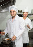 Two cooks at restaurant kitchen Royalty Free Stock Images