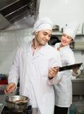 Two cooks at restaurant kitchen Stock Photo
