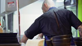 Two cooks prepares dishes at restaurant kitchen. Two cooks stands at the restaurant kitchen and prepares the dishes. Professional workers are making delicious stock footage