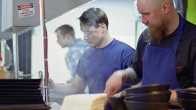 Two chefs are cooking at the restaurant kitchen. Two cooks stands at the restaurant kitchen and prepares the dishes. Professional workers are making delicious stock video footage