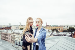 Two cool blond real girls friends making selfie on roof top, lifestyle people concept. Modern teens Royalty Free Stock Images