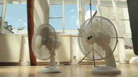Two cooling fans inside on a hot summer day stock video