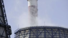 Two cooling towers emitting steam, with a blue sky background stock video footage