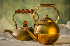Two copper teapot on paper. Green background, old, vintage Royalty Free Stock Photography