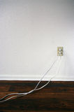 Two Cords Plugged In. Two white extension cords plugged into an electrical outlet on a white wall stock photo