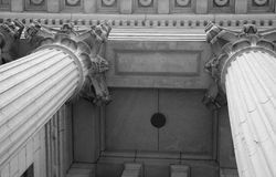 Two Corinthians. A black and white view of a set of ornate corinthian columns as well as the decorative ceiling of the portico Stock Images
