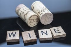 Two corks next to a few letters of wood with the word wine. Conceptual image stock photos