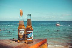 Two Corona Extra and San Mig Light Beers on Top of Brown Wooden Plank Near Beach Stock Image
