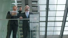 Two corporate executives discussing business using digital tablet. Two corporate executives standing on second floor of a glass and steel building discussing stock footage