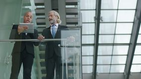 Two corporate executives discussing business using digital tablet. Two corporate executives in formal wear standing on second floor on a glass and steel building stock video footage