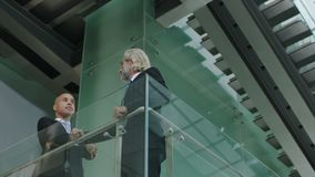 Two corporate executives in standing on second floor discussing business. Two corporate executives in full suit standing on second floor of a glass and steel stock video