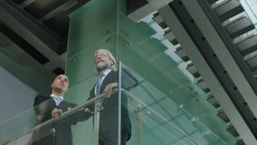 Two corporate executives in standing on second floor discussing business. Two corporate executives in full suit standing on second floor of a glass and steel stock footage
