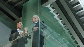 Two corporate executives standing on second floor discussing business. Two corporate executives standing on second floor holding a cup of coffee discussing stock video