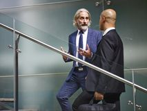 Two corporate executives talking while ascending stairs. Caucasian and latino corporate executives having a conversation while ascending stairs in modern office Royalty Free Stock Photography