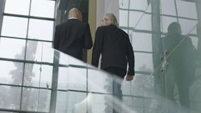 Two corporate executives talking while ascending stairs. Rear view of corporate executives talking while ascending stairs in modern office building Stock Images