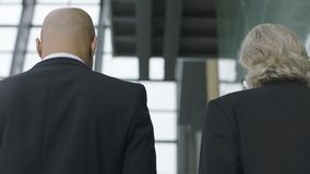 Two corporate executives talking while ascending stairs. Rear view of corporate executives talking while ascending stairs in modern office building Stock Photo
