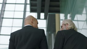 Two corporate executives talking discussing business while ascending stairs. Two corporate executives in full suit talking discussing business while ascending stock footage