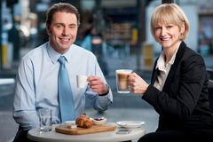 Two corporates discussing business over snacks. Two happy business people enjoying snacks in open-air restaurant Royalty Free Stock Photos