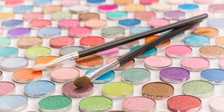 Two cosmetic brushes laying on colored eye shadows stock photography
