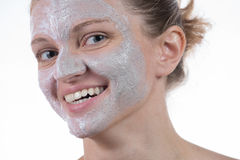 Two cosmetic mask of gray clay with scrub and cream on the face Royalty Free Stock Photos