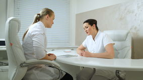 Two cosmeticians talking in the office room. Dolly shot of two cosmeticians in the office room discussing professional issues with pad on the table stock footage