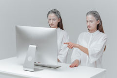 Two cosmic women sitting at the computer. Two cosmic fashion woman sitting at the computer. Girl pointing finger at the screen over gray background stock images