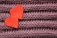Two cotton hearts on a knitted violet background stock photos